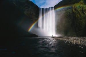 rainbow across waterfall